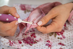 Closeup on seamstress unthread. In studio Royalty Free Stock Images