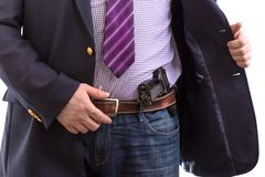 Closeup security agent in business suit with hand gun attached on belt. isolated on white royalty free stock photography