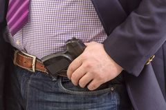 Closeup security agent in business suit with hand gun attached on belt.  on white royalty free stock photo