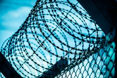 Closeup a security fence with barbed wire. Human Rights and social justice abstract concept stock image