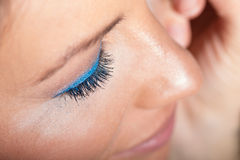 Closeup of eyelid. Closeup with selective focus of the eyelid and eyelashes of a young woman's face with glittering blue eye shadow Royalty Free Stock Photos