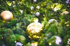 Closeup and selective focus of golden and silver bauble hanging. From a decorated Christmas tree with beautiful light and bokeh Royalty Free Stock Photography