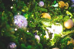 Closeup and selective focus of golden and silver bauble hanging. From a decorated Christmas tree with beautiful light and bokeh Royalty Free Stock Image