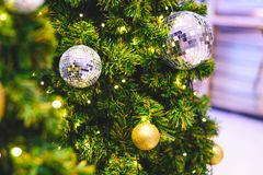 Closeup and selective focus of golden and silver bauble hanging. From a decorated Christmas tree with beautiful light and bokeh Stock Image