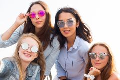 A close-up selfie of the four beautiful bridesmaids in colorful sunglasses on the background of the sky royalty free stock photos
