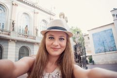 Closeup selfie-portrait of funny attractive girl tourist smiling. And taking selfie in the Figueres, Spain, next to the Museum of Salvador Dali. Travel blog royalty free stock image