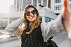 Closeup selfie portrait of joyful fashionable young woman in modern sunglasses, long blonde hair, knitted hat smiling on royalty free stock photography