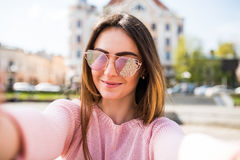 Closeup selfie-portrait student of attractive girl in sunglasses with long hairstyle and smile in city. Stock Photos