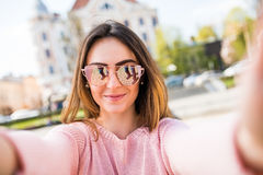 Closeup selfie-portrait student of attractive girl in sunglasses with long hairstyle and smile in city. Stock Image