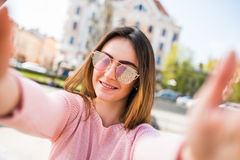 Closeup selfie-portrait student of attractive girl in sunglasses with long hairstyle and smile in city. Royalty Free Stock Image