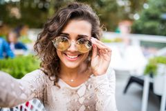 Closeup selfie-portrait student of attractive girl in sunglasses with curly hairstyle and snow-white smile in city. royalty free stock image