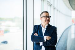 Closeup of a senior businessman with his arms folded near panoramic windows in an office interior. stock photo