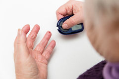 Closeup of senior hands with glucometer. Some female senior adult hands with glucometer royalty free stock photos
