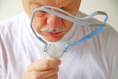 Older man holds CPAP headgear. Closeup of senior man with the headgear portion of a continuous positive airway pressure machine for sleep apnea royalty free stock photo