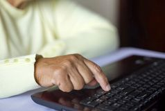 Closeup senior old woman hand on laptop keyboard surfing internet at home with free and copy space stock image