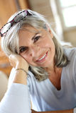 Closeup of senior woman with eyeglasses on hair Stock Image