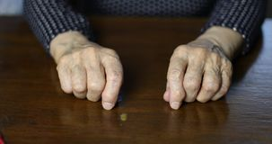 Closeup of senior woman hands with deep wrinkles. Grandma put her old hands on the table at home stock footage
