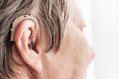 Closeup senior woman using hearing aid. Closeup senior woman with hearing aid in her ear. Health care, hear amplify, device for the deaf stock image