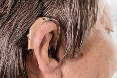 Closeup senior woman using hearing aid. Closeup senior woman with hearing aid in her ear. Health care, hear amplify, device for the deaf royalty free stock photos