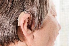 Closeup senior woman using hearing aid. Closeup senior woman with hearing aid in her ear. Health care, hear amplify, device for the deaf royalty free stock images
