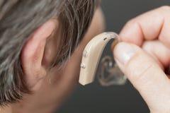 Closeup senior woman using hearing aid. Closeup senior woman with hearing aid in her ear. Health care, hear amplify, device for the deaf stock photo
