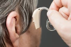 Closeup senior woman using hearing aid. Closeup senior woman with hearing aid in her ear. Health care, hear amplify, device for the deaf Stock Images