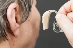 Closeup senior woman using hearing aid. Closeup senior woman with hearing aid in her ear. Health care, hear amplify, device for the deaf stock photos