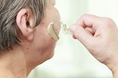 Closeup senior woman using hearing aid. Closeup senior woman with hearing aid in her ear. Health care, hear amplify, device for the deaf royalty free stock photo