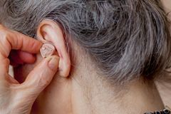 Closeup senior woman inserting hearing aid in her ears.  royalty free stock images
