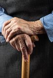 Closeup of senior woman's hands on walking stick. Closeup of senior woman's hands on wooden walking stick Stock Images
