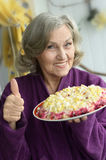Closeup of a senior woman. With salad and thumb up Royalty Free Stock Images