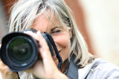 Closeup of senior woman tacking pictures Stock Image