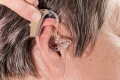 Closeup senior woman using hearing aid. Closeup senior woman with hearing aid in her ear. Health care, hear amplify, device for the deaf royalty free stock image