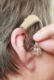Closeup senior woman using hearing aid. Closeup senior woman with hearing aid in her ear. Health care, hear amplify, device for the deaf royalty free stock photos