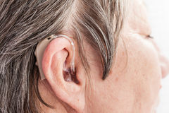 Closeup senior woman using hearing aid. Closeup senior woman with hearing aid in her ear. Health care, hear amplify, device for the deaf royalty free stock photography