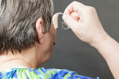 Closeup senior woman using hearing aid. Closeup senior woman with hearing aid in her ear. Health care, hear amplify, device for the deaf stock photography