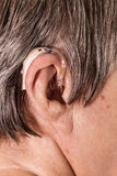 Closeup senior woman using hearing aid Royalty Free Stock Images