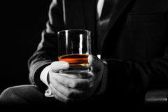 Closeup of serious businessman holding  whiskey illustrate executive privilege concept. Stock Image