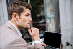 Closeup of serious businessman using modern laptop in coffee shop. Closeup of serious handsome businessman using modern laptop in coffee shop Stock Photos