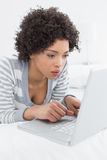 Closeup of a serious woman using laptop in bed Royalty Free Stock Photos