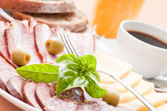Closeup of served breakfast. Coffe, juice, bread, cheese, cold meat, salami Royalty Free Stock Photography