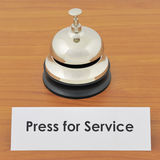 Closeup of service bell and sign on wooden desk Royalty Free Stock Photo