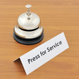 Closeup of service bell and sign on wooden desk Stock Images