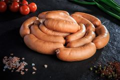 Closeup set of raw short sausages with onion and tomatoes. Closeup set of raw short thick meat sausages served with pink salt, spices, green onion and tomatoes stock image