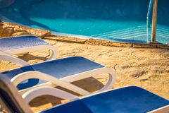 Closeup several of sun loungers by a beautiful swimming pool. Royalty Free Stock Image