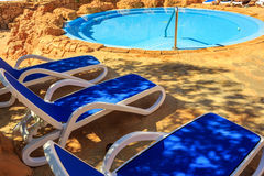 Closeup several of sun loungers by a beautiful swimming pool. Stock Photo