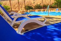 Closeup several of sun loungers by a beautiful swimming pool. Stock Image