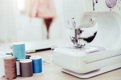 Closeup of sewing machine with fashion designer showroom studio workshop background with new collection of pink pastel female