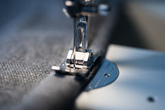 Closeup of sewing machine foot and needle. Double hem of a grey sofa cover stock photo