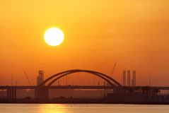 Closeup of the Shaikh Khalifa bridge & sun at sunrise, Bahrain Royalty Free Stock Images